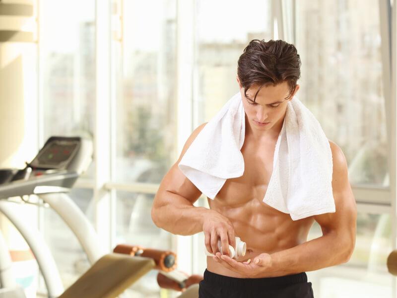 筋トレ後にサプリメントを飲む男性