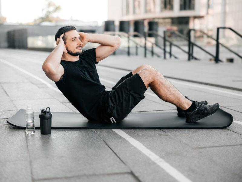 トレーニングマットで腹筋を鍛える男性