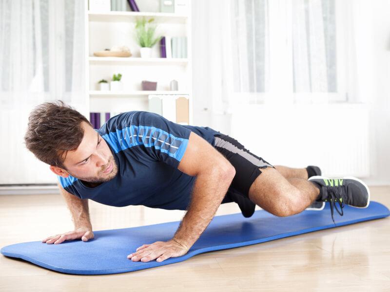 トレーニングマットで腕立てをする男性