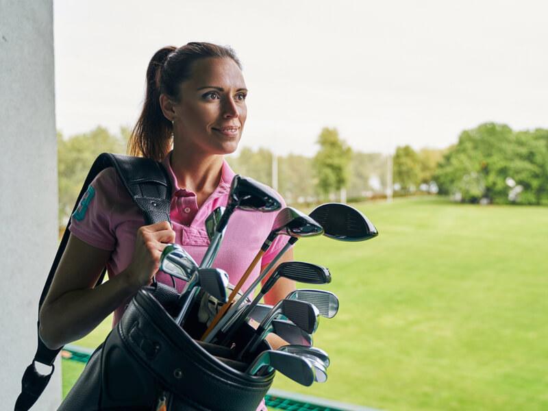 ゴルフバッグを持つ女性