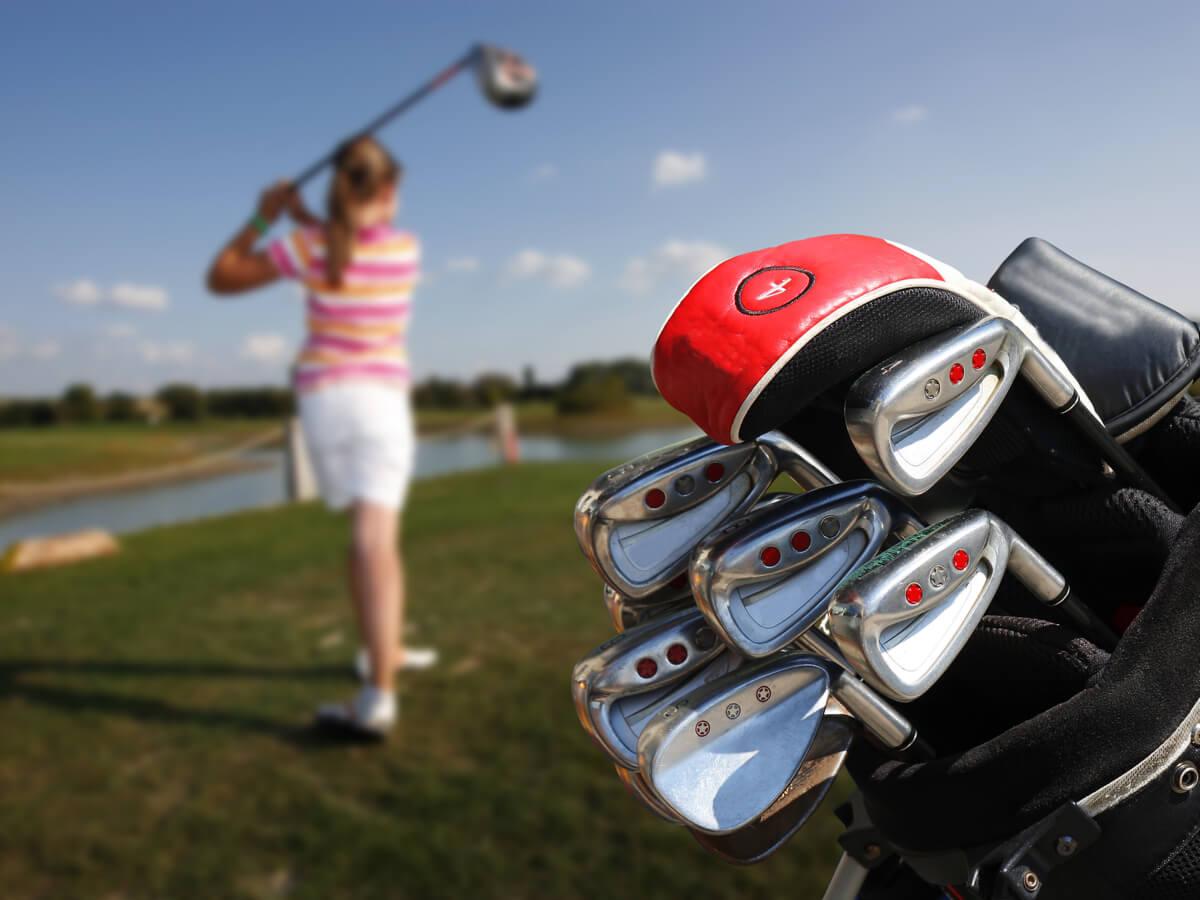 ゴルフバッグとゴルフをしている女性
